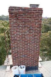 A historic brick chimney in very bad shape
