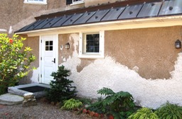 Portland cement mortar removed and lime stucco restored with a Harling finish to match the original stucco